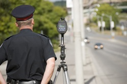 A policeman waits to catch speeding drivers with a radar gun