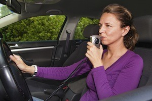 Woman in car blowing into breathalyzer